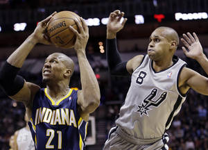 Photo - Indiana Pacers' David West (21) looks to shoot in front of San Antonio Spurs' Patty Mills (8), of Australia, during the first half on an NBA basketball game, Saturday, Dec. 7, 2013, in San Antonio. (AP Photo/Eric Gay)