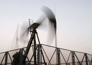 Photo - FILE - In this Monday, June 10, 2013, file photo, an oil pump jack works at sunset in the desert oil fields of Sakhir, Bahrain. While the price of U.S. benchmark oil rose 58 cents to $107.43 per barrel in afternoon trading Thursday, Aug. 15, 2013  inflated by turmoil and increasing violence in the Middle East,  ample global oil supplies are helping to keep the rise in check. (AP Photo/Hasan Jamali, File)
