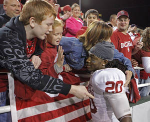 Photo - Quinton Carter (20) gets a hug from fans following the college football game between the University of Oklahoma Sooners (OU) and the Baylor Bears (BU) at Floyd Casey Stadium on Saturday, November 20, 2010, in Waco, Texas.   Photo by Steve Sisney, The Oklahoman
