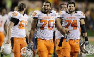 Photo - Oklahoma State University's Jonathan Rush (70), Grant Garner (74) and other players walk off the field after defeating Texas in an NCAA college football game, Saturday, Nov. 13, 2010 in Austin, Texas. Oklahoma State won 33-16. (AP Photo/Eric Gay)