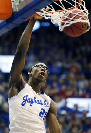 Photo - Kansas center Joel Embiid dunks during the first half of an NCAA college basketball game against Kansas State in Lawrence, Kan., Saturday, Jan. 11, 2014. (AP Photo/Orlin Wagner)