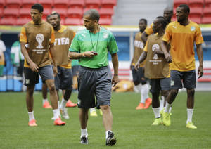 Photo - Ivory Coast coach Sabri Lamouchi, center, walks on the pitch a training session at the Estadio Nacional in Brasilia, Brazil, Wednesday, June 18, 2014. Ivory Coast plays in group C of the 2014 Brazil soccer World Cup. (AP Photo/Sergei Grits)