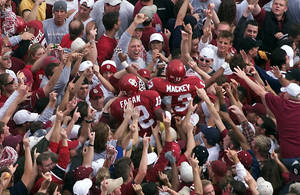 Photo - OU fans surround Oklahoma players Curtis Fagan (12) and Damian Mackey (13) as the players make their way off the field after beating the number-one ranked Nebraska Cornhuskers 31-14 in Norman, Okla., Saturday, Oct. 28, 2000. (AP Photo/J.Pat Carter)
