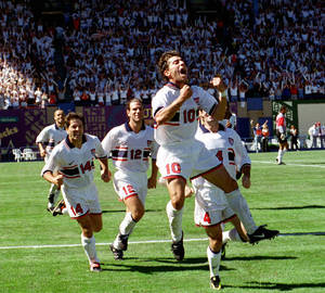 Photo - FILE - In this Sept. 7, 1997 file photo, U.S. National soccer team midfielder Tab Ramos (10) is followed by teammates as he celebrates his game-winning goal during their World Cup final round qualifying game against Costa Rica in Portland, Ore. While Ramos was a central figure in the early days of the current American streak of qualifying for seven straight World Cups, playing in the first three of those from 1990-98, it wasn't until 2006 that the U.S. Soccer Federation began to study its development system in earnest. (AP Photo/Don Ryan, File)