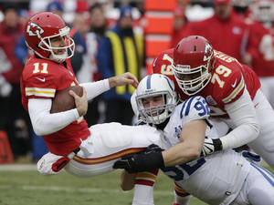 Photo - Kansas City Chiefs quarterback Alex Smith (11) is sacked by Indianapolis Colts outside linebacker Bjoern Werner (92) during the first half of an NFL football game at Arrowhead Stadium in Kansas City, Mo., Sunday, Dec. 22, 2013. Chiefs tackle Donald Stephenson (79) tries to block on the play. (AP Photo/Charlie Riedel)