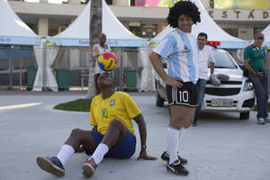 Photo - CORRECTING MARADONA ON THE RIGTH - The street performing mime, Daniel Gonzalez, righ, who is dressed to resemble Argentine soccer great Diego Armando Maradona, looks back at Marcio Pereira, dressed up as Brazilian soccer great Pele as he controlls the ball in front of Maracana stadium, Rio de Janeiro, Brazil, Wednesday, June 11, 2014. The World Cup soccer tournament starts Thursday. (AP Photo/Leo Correa)