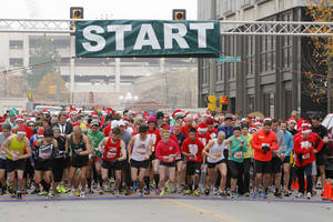 Photo - Runners begin the SandRidge Santa Run in downtown Oklahoma City in 2012. <strong>PAUL HELLSTERN - The Oklahoman</strong>
