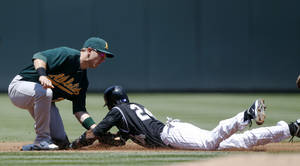 Photo -   Oakland Athletics shortstop Cliff Pennington, left, applies the tag to put out Colorado Rockies' Dexter Fowler as he tries to steal second base in the first inning of an interleague baseball game in Denver on Thursday, June 14, 2012. (AP Photo/David Zalubowski)