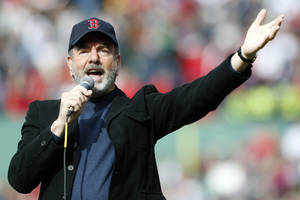 "Photo - FILE - This April 20, 2013 file photo shows Neil Diamond singing ""Sweet Caroline"" in the eighth inning of a baseball game between the Boston Red Sox and the Kansas City Royals in Boston. Sales for Neil Diamond's ""Sweet Caroline"" are up by 597 percent a week after the tune has become a source of comfort following bombings in Boston last week. The song is a staple of Boston Red Sox games. Nielsen SoundScan said Wednesday that it sold 19,000 tracks this week. It only sold 2,800 the week before. It has sold 1.75 million tracks to date. Diamond released the song in 1969. It is addressed to Caroline Kennedy. (AP Photo/Michael Dwyer, file)"