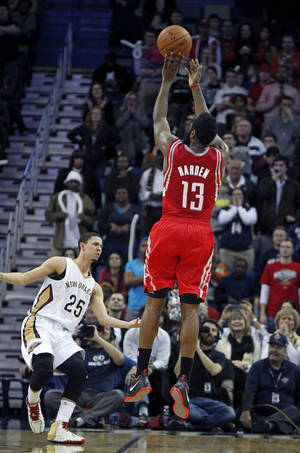 Photo - Houston Rockets shooting guard James Harden (13) shoots the go-ahead jumper over New Orleans Pelicans shooting guard Austin Rivers (25) with 28 seconds in the second half of an NBA basketball game in New Orleans, Wednesday, Jan. 15, 2014. The Rockets won 103-100. (AP Photo/Gerald Herbert)