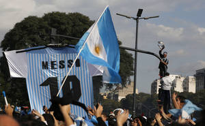 Photo - Soccer fans gather at the obelisk to welcome home Argentina's soccer team, before it was announced that the team won't be coming to this landmark for a welcome ceremony after they landed at the airport in Buenos Aires, Argentina, Monday, July 14, 2014. Fans came out to welcome home Argentina's team after it was defeated 1-0 by Germany at the Brazil World Cup final match on Sunday. (AP Photo/Jorge Saenz)