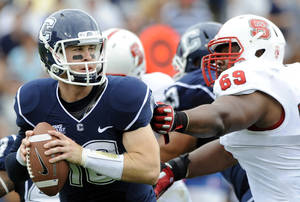 Photo -   Connecticut's Chandler Whitmer, left, is pressured by North Carolina State's Thomas Teal during the first half of their football game in East Hartford, Conn., on Saturday, Sept. 8, 2012. (AP Photo/Fred Beckham)