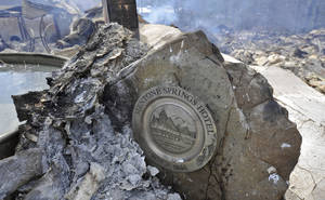 """Photo - A sign sits among the remains and debris from the 130 year old Mentone Springs Hotel and White Elephant Antique Galleries on Monday, March 3, 2014 in Mentone, Ala.  A fire ripped through the Mentone Springs Hotel Saturday night and authorities are unsure of the cause of the fire.  The Mentone Springs Hotel was one of the oldest hotels in the state of Alabama and was featured in The New York Times best-seller """"1,000 Places to See Before You Die."""" Built with 57 rooms in 1884 by Dr. Frank Caldwell of Pennsylvania, the hotel was named after Mentone in France after Caldwell's daughter saw news reports of Queen Victoria visiting there. (AP Photo/AL.com, Bob Gathany)"""