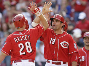Photo - Cincinnati Reds' Chris Heisey (28) is congratulated by Joey Votto (19) after Heisey hit a pinch-hit grand slam off Tampa Bay Rays relief pitcher Josh Lueke in the eighth inning of a baseball game, Sunday, April 13, 2014, in Cincinnati. Cincinnati won 12-4. (AP Photo/Al Behrman)