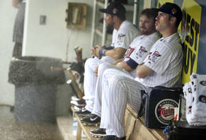 Photo - Minnesota Twins first baseman Joe Mauer, right, sits in the dugout with teammates during a heavy rain before a scheduled exhibition baseball game against the St. Louis Cardinals, Thursday, March 6, 2014, in Fort Myers, Fla. (AP Photo/Steven Senne)
