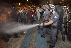Photo - A police officer pepper sprays strikers and protesters during a clash with riot police in front of the Ana Rosa metro station, in an ongoing subway strike by operators, in Sao Paulo, Brazil, Monday, June 9, 2014. Authorities are deeply worried about the strike because the subway is the main means of transportation for World Cup fans scheduled to attend Thursday's opening match when Brazil takes on Croatia. The stadium is about 20 kilometers (12 miles) east of central Sao Paulo, where most tourists stay. (AP Photo/Mario Angelo)