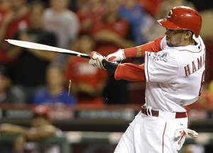 Photo - Cincinnati Reds' Billy Hamilton hits a broken bat single off Chicago Cubs relief pitcher Hector Rondon to drive in the winning run in the bottom of the ninth inning of a baseball game, Tuesday, July 8, 2014, in Cincinnati. Cincinnati won 6-5. (AP Photo/Al Behrman)