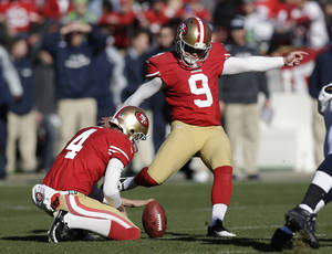 Photo - San Francisco 49ers kicker Phil Dawson (9) boots a field goal as Andy Lee, left, holds the ball in the first half of an NFL football game against the Seattle Seahawks, Sunday, Dec. 8, 2013, in San Francisco. (AP Photo/Marcio Jose Sanchez)