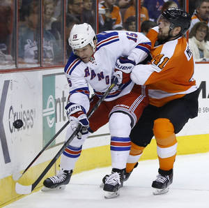 Photo - New York Rangers' Derek Dorsett, left, and Philadelphia Flyers' Andrej Meszaros battle for the puck during the third period of an NHL hockey game, Sunday, March 2, 2014, in Philadelphia. Philadelphia won 4-2. (AP Photo/Matt Slocum)
