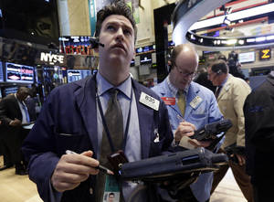 Photo - FILE - In this March 7, 2014 file photo, Glenn Kessler, left, works with fellow traders on the floor of the New York Stock Exchange. World stock markets steadied Tuesday, March 11, 2014 after a sell-off the day before. (AP Photo/Richard Drew, File)