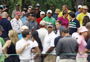 photo -   Fans and officials help Tiger Woods, center back, look for his lost golf ball on the fifth hole during the second round of the Wells Fargo Championship golf tournament at Quail Hollow Club in Charlotte, N.C., Friday, May 4, 2012. Woods was given a free drop after it was determined the ball was picked up by a fan. (AP Photo/Nell Redmond)