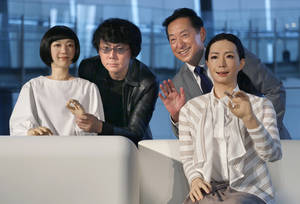 Photo -  Japanese android expert Hiroshi Ishiguro, second left, and National Museum of Emerging Science and Innovation Miraikan Chief Executive Director Mamoru Mohri, second right, pose Tuesday with a female-announcer robot called Otonaroid, right, and a girl robot called Kodomoroid during an unveiling of the museum's new guides in Tokyo. The latest creations from Osaka University Prof. Ishiguro are the Otonaroid, the Kodomoroid and Telenoid, a hairless mannequin head with pointed arms that serves as a cuddly companion. The robots with silicon skin and artificial muscles were shown to reporters at Miraikan museum. AP Photo  <strong>Shizuo Kambayashi -   </strong>