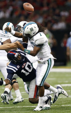 Photo -   Mississippi defensive end C.J. Johnson (10) knocks the ball from Tulane quarterback Devin Powell (1) during the first half of an NCAA college football game in Saturday, Sept. 22, 2012. in New Orleans. (AP Photo/Bill Haber)