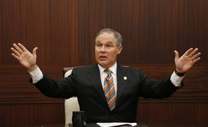 Photo - Oklahoma Attorney General Scott Pruitt gestures as he answers a question during a news conference in Oklahoma City, Tuesday, July 16, 2013. Pruitt and the attorney generals of 11 other states have filed a lawsuit seeking documents involving the Environmental Protection Agency's legal strategy with environmental groups. (AP Photo/Sue Ogrocki)