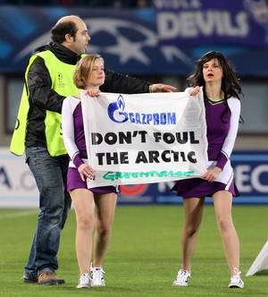 Photo - A guard escourts two Greenpeace activists carrying a banner from the field before the Champions League Group G soccer match between Austria Vienna and Zenit St. Petersburg in Vienna, Austria, Wednesday, Dec. 11, 2013. (AP Photo/Ronald Zak)