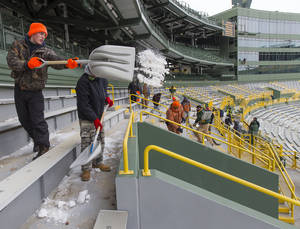 Photo - Workers clear ice and snow from the seats at Lambeau Field on Friday, Jan. 3, 2014, in Green Bay, Wis. in preparation for Sunday's NFL football wild-card playoff game between the Green Bay Packers and San Francisco 49ers.(AP Photo/Mike Roemer)