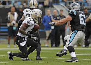 Photo - New Orleans Saints' Malcolm Jenkins (27) returns an interception as Carolina Panthers' Ryan Kalil (67) tries to make the tackle in the first half of an NFL football game in Charlotte, N.C., Sunday, Dec. 22, 2013. (AP Photo/Chuck Burton)