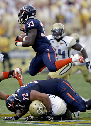 "Photo -   FILE - In this Sept. 15, 2012, file photo, Virginia running back Perry Jones (33) jumps over teammate Oday Aboushi (72) and Georgia Tech linebacker Jeremiah Attaochu, bottom, during the first quarter of an NCAA college football game in Atlanta. Virginia's players say the signs of improvement are all there. The offensive line has come together and Perry Jones, the player they call ""Superman,"" has actually been seen running into gaping holes the past few weeks. Jones and the Cavaliers hope it shows when they host Maryland on Saturday. (AP Photo/David Goldman, File)"
