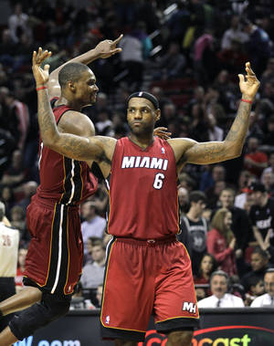 Photo - Miami Heat's LeBron James (6) and teammate Chris Bosh celebrate their victory over the Portland Trail Blazers during an NBA basketball game Sunday, Jan. 9, 2011, in Portland, Ore. The Heat defeated the Trail Blazers 107-100.  (AP Photo/Rick Bowmer) ORG XMIT: ORRB108