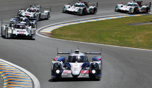 Photo - The Toyota TS040 Hybrid  driven by Japanese driver Kazuki Nakajima, France's Stephane Sarrazin and Austria's Alexander Wurtz, foreground, takes a bend during the 82th 24-hour Le Mans endurance race, in Le Mans, western France, Saturday, June 14, 2014. (AP Photo/Bob Edme)