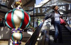 "Photo - A woman rides the escalator past a giant holiday ornament at the CambridgeSide Galleria mall in Cambridge, Mass., Monday, Dec. 24, 2012. Although fresh data on the holiday shopping season is expected in coming days, early figures point to a ho-hum season for retailers despite last-ditch efforts to lure shoppers over the final weekend before Christmas. And with concerns about the economy and the looming ""fiscal cliff"" weighing on the minds of already cautious shoppers, analyst say stores will need to offer ""once in a lifetime"" blowouts to clear out inventory.  (AP Photo/Michael Dwyer)"