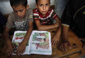 Photo - Palestinian boys read at a United Nations school where dozens of families have sought refuge after fleeing their homes following heavy Israeli forces' strikes in Beit Hanoun, northern Gaza Strip, Saturday, July 19, 2014. (AP Photo/Lefteris Pitarakis)