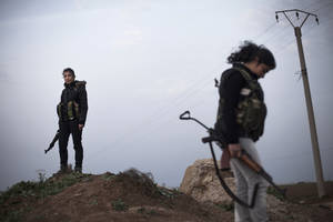 photo - Kurdish female members of the Popular Protection Units stand guard at a check point near the northeastern city of Qamishli, Syria, Sunday, March 3, 2013. (AP Photo/Manu Brabo)