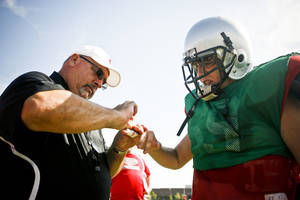 photo - HIGH SCHOOL FOOTBALL: Generals coach Dan Burgess tapes the finger of outside linebacker Jimmy Kiplinger (69) during a scrimmage at U.S. Grant High School on Saturday, Aug. 13, 2011. Photo by Zach Gray, The Oklahoman ORG XMIT: KOD
