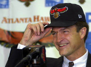 photo - BASKETBALL: Lon Kruger puts on an Atlanta Hawks hat as he is introduced as the new head coach of the team during a press conference at Philips Arena in Atlanta Thursday, May 25, 2000. Kruger was the coach at Illinois from 1997 - 2000 and replaces Lenny Wilkens, who resigned from the position on April 24. (AP Photo/John Bazemore)