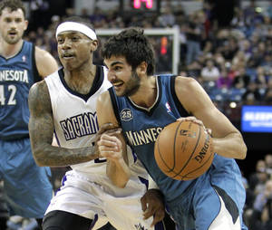 Photo - Minnesota Timberwolves guard Ricky Rubio, of Spain, right, drives to the basket past Sacramento Kings guard Isaiah Thomas during the first quarter of an NBA basketball game in Sacramento, Calif., Saturday, March 1, 2014.(AP Photo/Rich Pedroncelli)