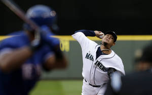 Photo - Seattle Mariners starting pitcher Felix Hernandez, right, throws against Texas Rangers' Adrian Beltre in the first inning of a baseball game on Saturday, May 25, 2013, in Seattle. (AP Photo/Elaine Thompson)