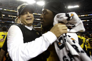 Photo - Missouri head coach Gary Pinkel and defensive lineman Markus Golden (33) embrace after beating Oklahoma State 41-31 at the Cotton Bowl NCAA college football game, Friday, Jan. 3, 2014, in Arlington, Texas.  (AP Photo/Tim Sharp)