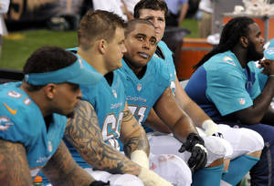 Photo - Miami Dolphins guard Richie Incognito (68) and tackle Jonathan Martin (71) look up from the bench in the second half of an NFL football game against the New Orleans Saints in New Orleans, Monday, Sept. 30, 2013. The Saints won 38-17. (AP Photo/Bill Feig)