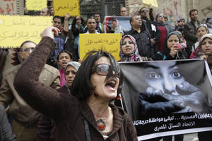 "photo -   FILE - In this Friday, March 16, 2012 file photo, an Egyptian activist chants slogans during a demonstration against an army doctor accused of public obscenity filed by a protester who claimed she was forced to undergo a virginity test, in front of Cairo's high court, in Egypt. Women protesters and rights groups have accused Egyptian military and prison authorities of sexual assault and abuse on female detainees in the latest crackdown on demonstrations. Arabic on the poster, center, reads, ""March 9, 2011, protesters torture "" and the banner, left, reads, ""we do not want the Egyptian woman to be a second-class citizen."" (AP Photo/Amr Nabil, File)"