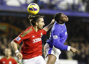 Photo - Swansea City's Chico, left, and Everton's Victor Anichebe in action during the English Premier League soccer match at Goodison Park, Liverpool, England, Saturday Jan. 12, 2013. The match ended in a 0-0 draw. (AP Photo/PA, Peter Byrne) UNITED KINGDOM OUT