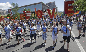 "Photo - In this June 8, 2014, photo, American Express workers carry giant, cutout letters that spelled, ""Love=Love,"" the theme of the of the gay pride parade, in Salt Lake City. Corporations have increased visibility this summer at gay pride parades around the country as same-sex marriage bans fall in the courts and polls show greater public acceptance of gay marriage. (AP Photo/Rick Bowmer)"