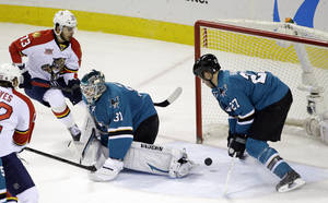 Photo - Florida Panthers' Brandon Pirri (73) scores past San Jose Sharks goalie Antti Niemi (31), of Finland, and defenseman Scott Hannan (27) during the second period of an NHL hockey game on Tuesday, March 18, 2014, in San Jose, Calif. (AP Photo/Marcio Jose Sanchez)