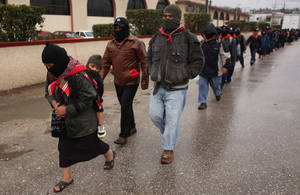 photo - Masked Mayan Indians who are members of the Zapatista National Liberation Army (EZLN) march in line to the mayor&#039;s office in San Cristobal de las Casas, Chiapas state, Mexico, Friday, Dec. 21, 2012. On Friday, Zapatistas in several cities are marching to the city mayor&#039;s office for a gathering where they will listen to a message from their leaders. (AP Photo/Ivan Castaneira)