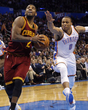 Photo - Oklahoma City's Russell Westbrook (0) tries to stop Cleveland's Kyrie Irving (2) during the NBA basketball game between the Oklahoma City Thunder and the Cleveland Cavaliers at the Chesapeake Energy Arena in Oklahoma City, Okla. on Wednesday, Feb. 26, 2014.  Photo by Chris Landsberger, The Oklahoman
