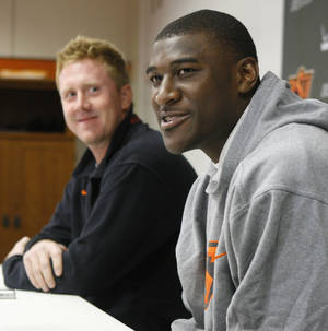 Photo - Oklahoma State All-America receiver Justin Blackmon, right, answers a question at a news conference in Stillwater, Okla., Wednesday, Jan 12, 2011. Both he and quarterback Brandon Weeden, left, will return for another season.  (AP Photo/Sue Ogrocki)